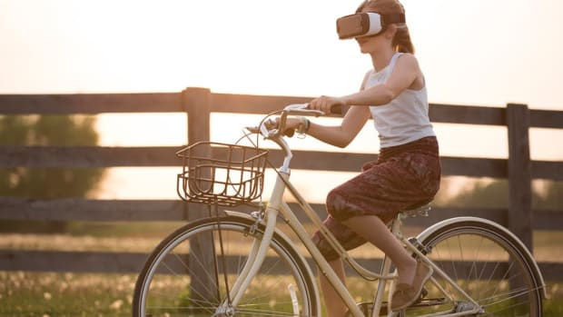 girl riding bicycle wearing VR headset