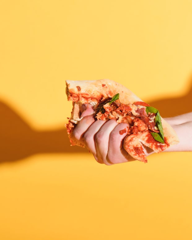 DP pizza SMUSHED Partial view of woman squeezing piece of pizza in hand on yellow background - null