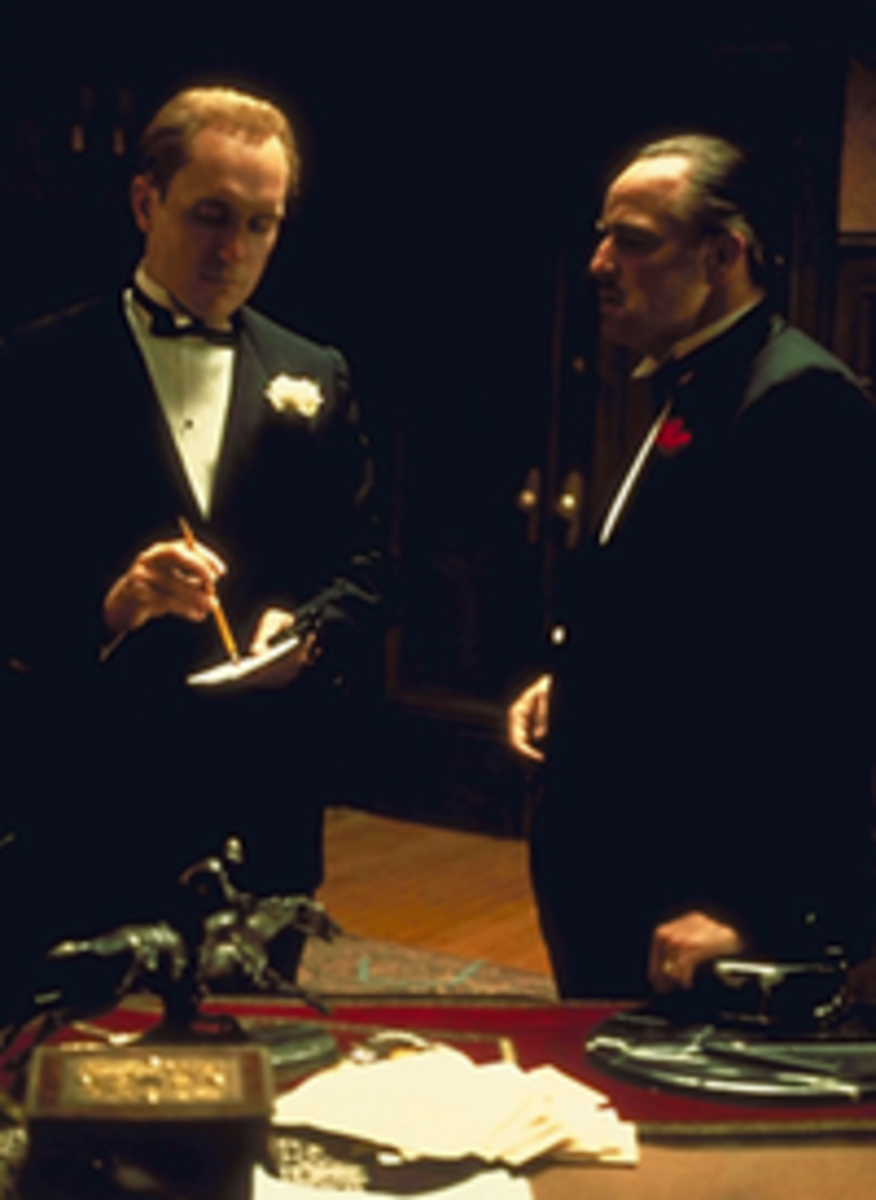 Tom teaches Michael about the action necessary to defend family while Vito counsels with wisdom in The Godfather.