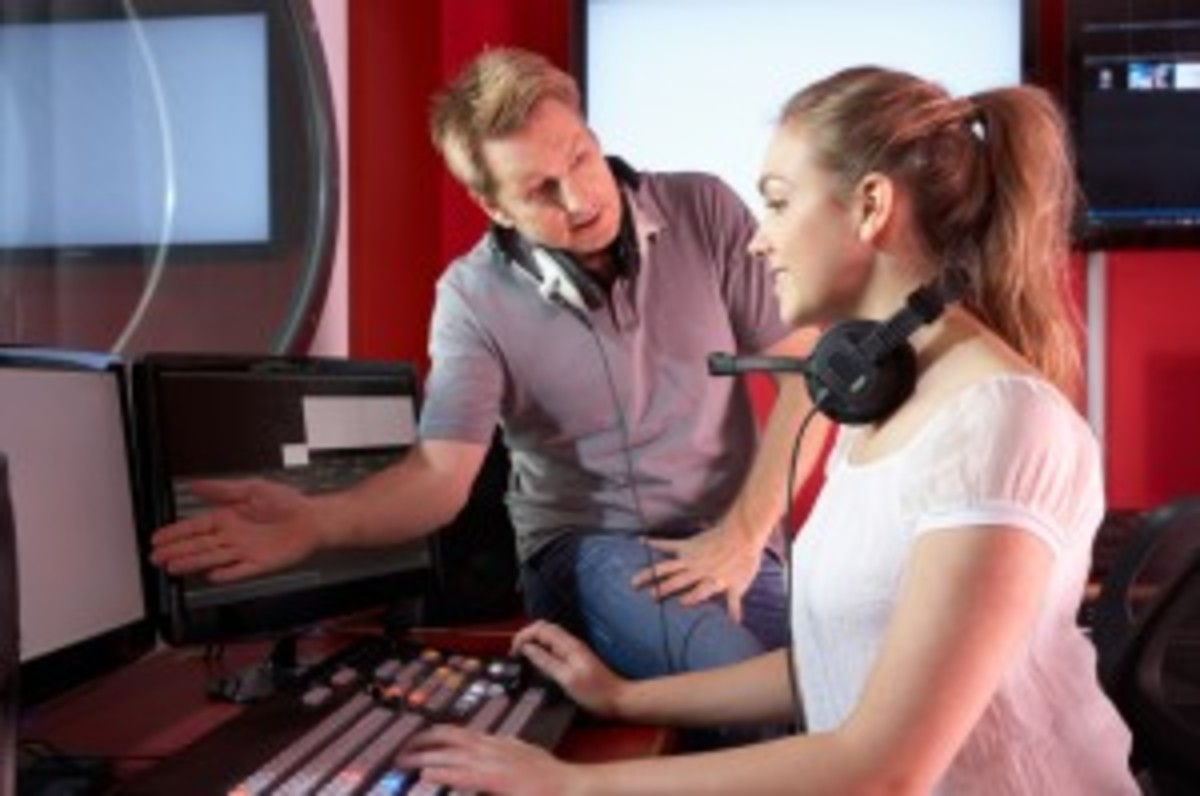 Media Student With Tutor Working In Film Editing Class