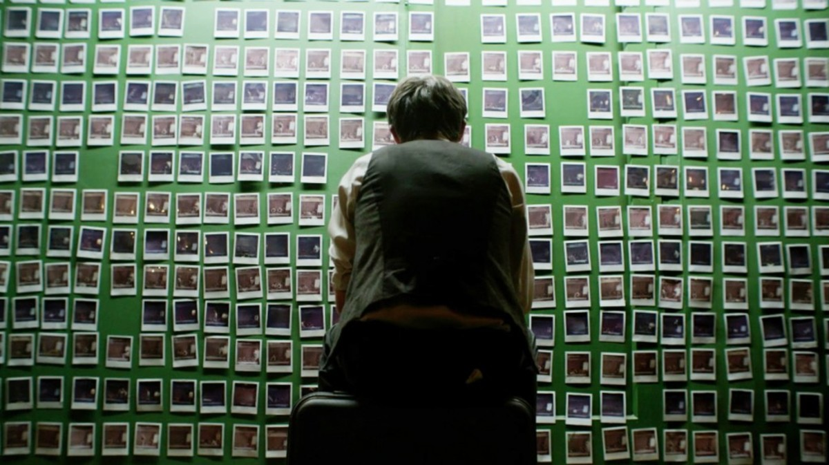 Matt O'Leary as Finn contemplates a wall of exposed Polaroids in a scene from TIME LAPSE, directed by Bradley King. PHOTO: XLrator Media