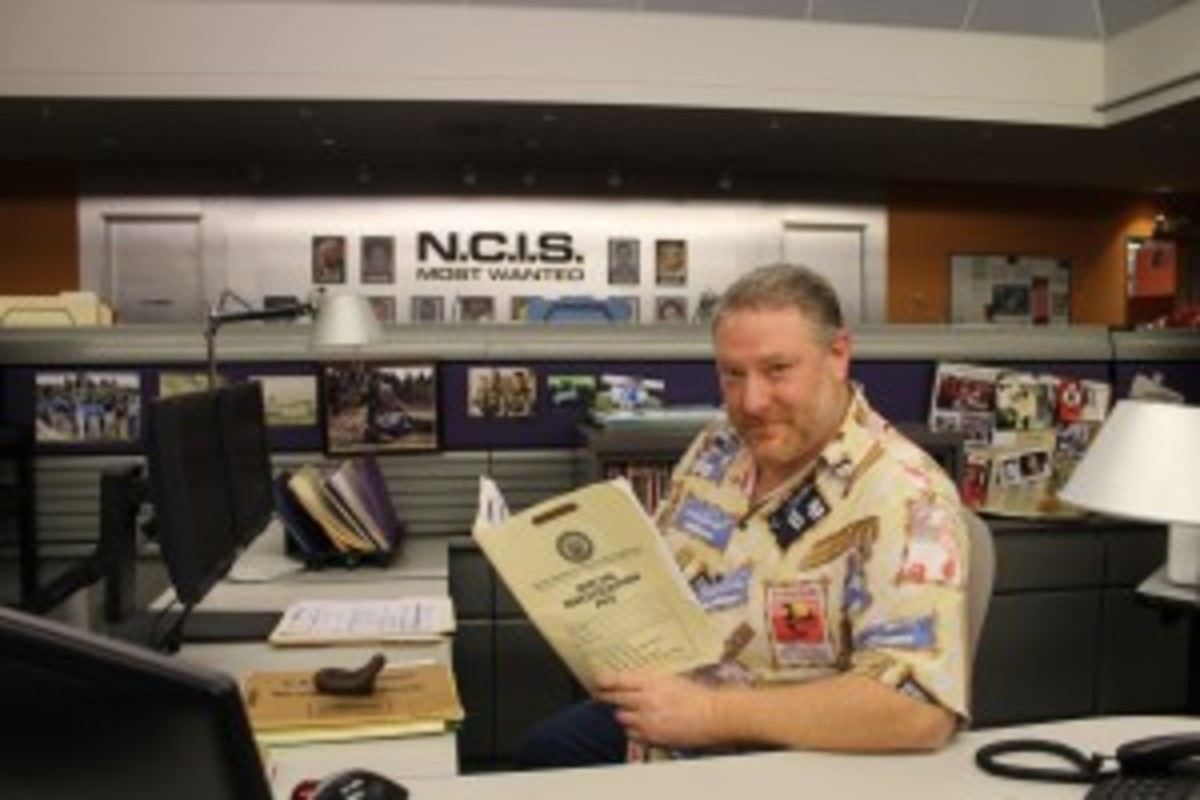 Michael sitting at Leon Gibbs' desk on the NCIS soundstage.