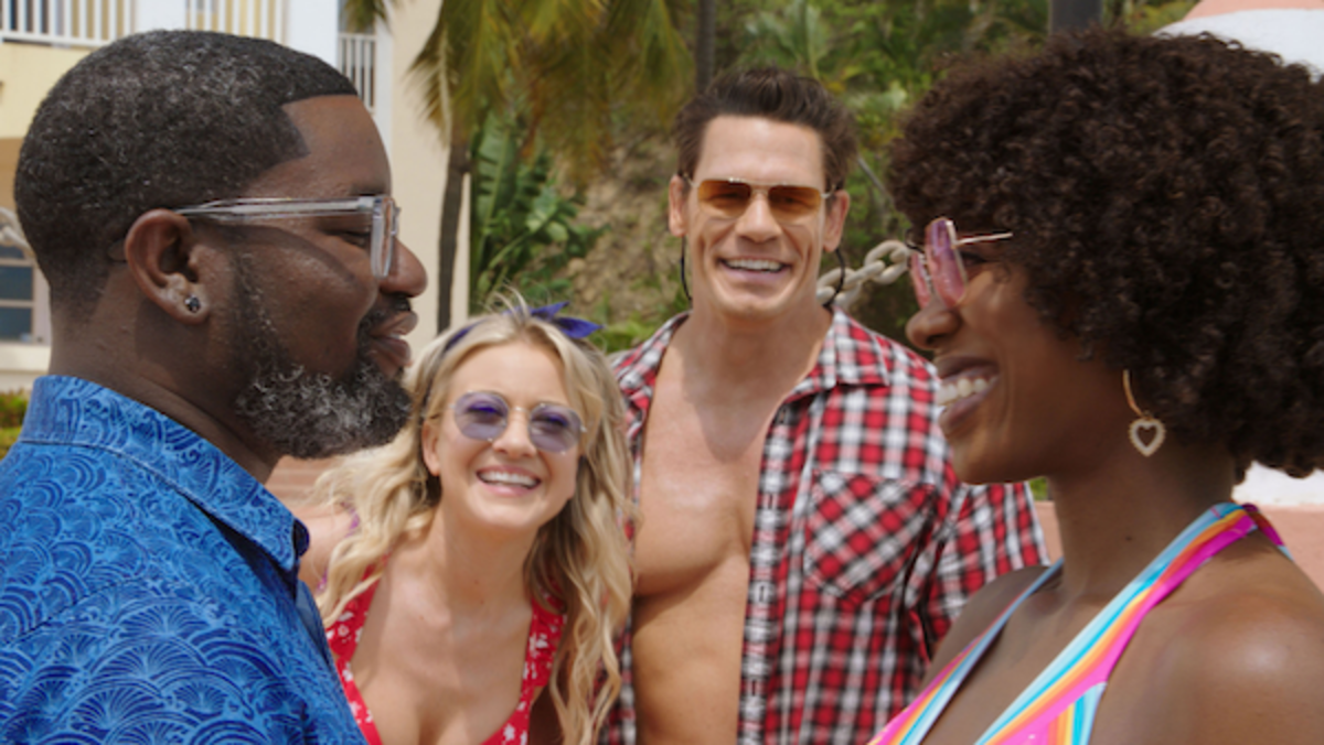 (L-R): Lil Rel Howery as Marcus, Meredith Hagner as Kyla, John Cena as Ron and  Yvonne Orji as Emily in 20th Century Studios' VACATION FRIENDS, exclusively on Hulu. Photo courtesy of 20th Century Studios. © 2021 20th Century Studios. All Rights Reserved.